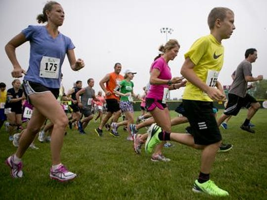Runners take off at the starting line Saturday during the 2014 Mike's Run at Jack Hackman Field in Marshfield.