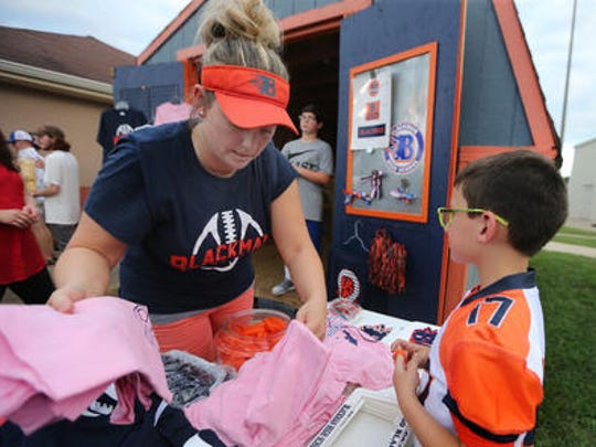 Crystal Brown and son Mason Brown, 9, man the Blackman football booster booth during the jamboree game at the school Thursday in August, 2016.