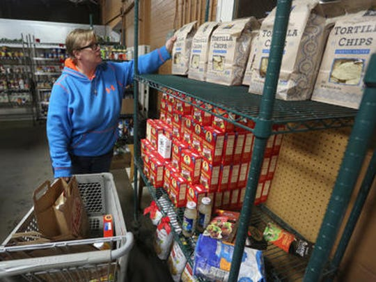 A volunteer gets food ready that will delivered to