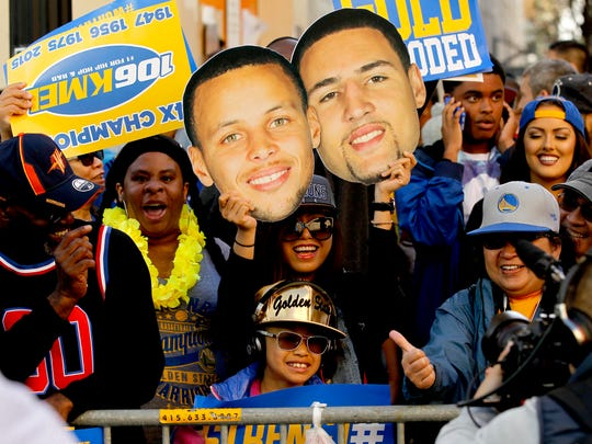 Fans cheer during the Golden State Warriors 2015 championship celebration in downtown Oakland.