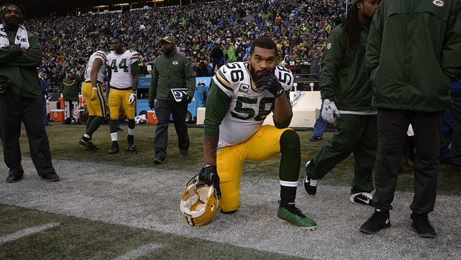 Green Bay Packers linebacker Julius Peppers dejectedly kneels on the sideline after losing to the Seattle Seahawks in overtime in Sunday's NFC championship game at CenturyLink Field in Seattle.