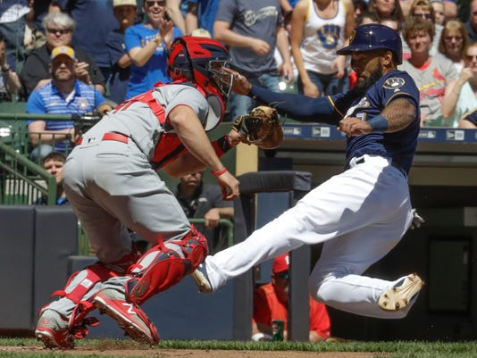 Milwaukee Brewers' Eric Thames slides safely past St. Louis Cardinals catcher Eric Fryer during the first inning of a baseball game Sunday, April 23, 2017, in Milwaukee. Thames scored from first on a ball hit by Ryan Braun. (AP Photo/Morry Gash)