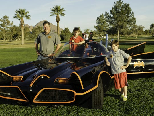 Philanthropist Charles Keller poses with his two sons and the Batmobile in Phoenix.