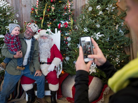 "From the left, eighteen month old Knox feels better about Santa when Knox's grandfather Chris Frazer sits on Santa's lap too. Richard Gibbs, playing Santa Claus, said that he was ""scared to death"" himself the first time his father took him to see Santa at the Bon-Ton when it was in downtown York at Beaver and Market Streets. Mother Sara Yanavitch, right, takes a picture."