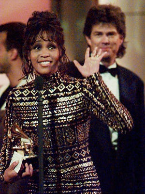 "Whitney Houston waves to the crowd at the 36th Annual Grammy Awards in New York on March 1, 1994 after she was honored for Record of the Year, ""I'll Always Love You,"" and Album of the Year, the soundtrack from the film ""The Bodyguard."" At rear is her producer David Foster, who shared the honors with her."
