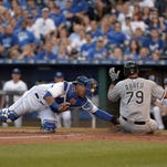 Kansas City Royals catcher Salvador Perez (13) misses the tag as Chicago White Sox first baseman Jose Abreu (79) scores in the first inning at Kauffman Stadium Friday night.