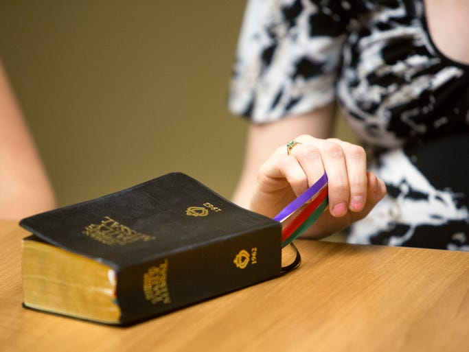 Jennifer Trapuzzano pulls the markers in a 1962 Roman Catholic Daily Missal that belonged to her husband, Nathan Trapuzzano, as she recalls the day they met.  Nathan Trapuzzano, 24, was gunned down near a tire shop during a morning walk April 1.