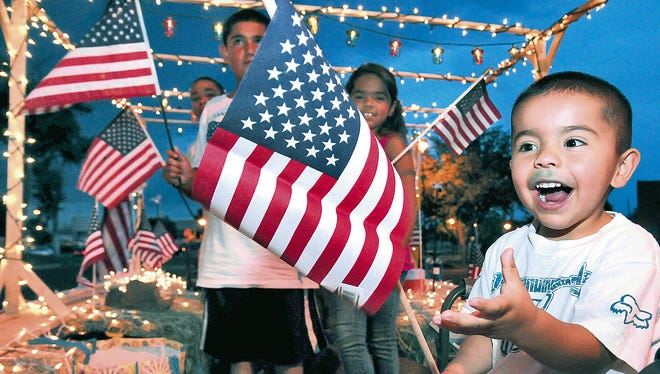 Jacob Lopez gets excited when handed an American Flag while riding in the Lopez Glass float on Wednesday during the 2013 Electric Light Parade.