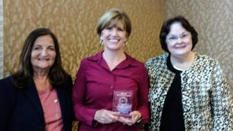 Missy Schraeder (center), accompanied by DuBard School director Dr. Maureen K. Martin (right), accepts the IMSLEC Innovator Award as an Outstanding Educator in a College or University from IMSLEC president Dr. Mary L. Farrell (left) of Fairleigh Dickinson University in New Jersey.