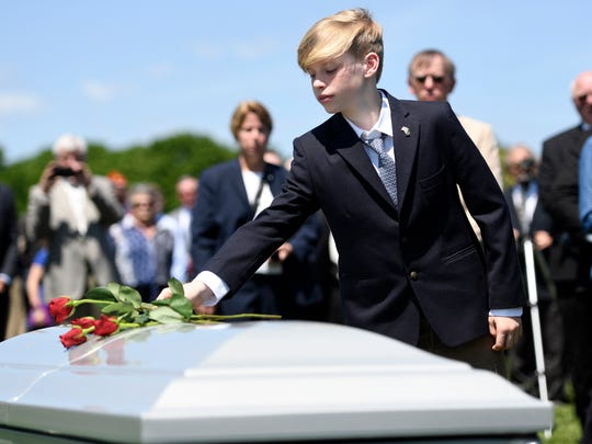 Tyler Ryan, 13, places a rose on his grandfather's