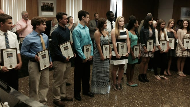 Members of the boys and girls track teams of Grace Christian School hold plaques received from the Rapides Parish Police Jury during a recent jury meeting. Both teams won Class B state championships in the Louisiana High School Athletic Association state meet. Some members of the teams were not able to attend the Police Jury ceremony honoring the teams and coaches.