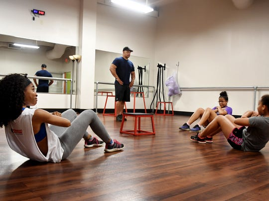 Rodney Stephenson counts the sit-ups done by his three daughters, 16-year-old Nylah, 15-year-old Eliese, and 11-year-old Melony during their evening workout session at Anytime Fitness in Jackson.
