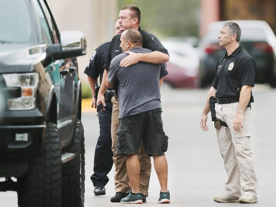 Fort Myers police officers comfort one another recently