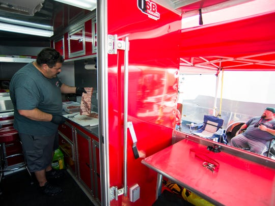 Michael Licciardello of Sir-Porks-Alot-BBQ trims his ribs inside his custom mobile smoker Friday, July 7, 2017 in Wildwood.