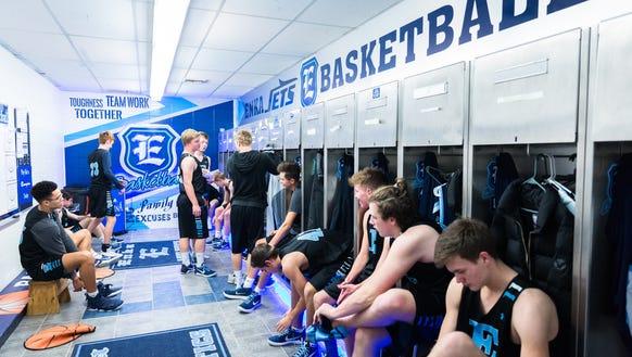 The Enka boys basketball team dresses for practice