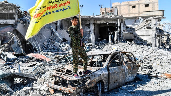 A member of the Syrian Democratic Forces  holds its flag at Al-Naim square in Raqqa on Oct. 17, 2017.