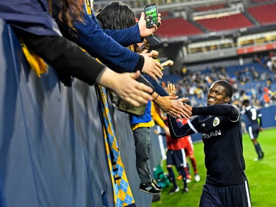 Nashville SC's  Lebo Moloto, 10, gives high fives to