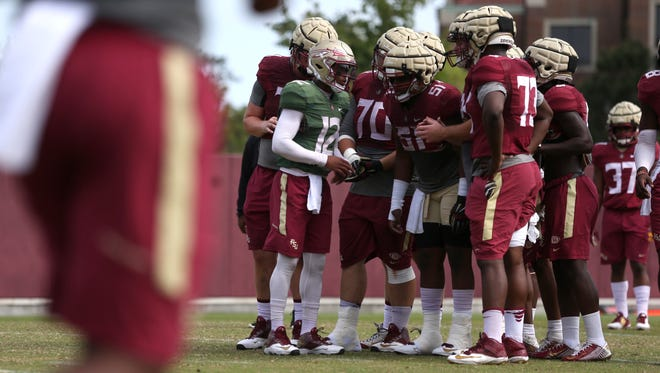 FSU quarterback Deondre Francois talks to his teammates in a huddle during spring practice at the Dunlap Training Facility on Thursday, March 30, 2017.