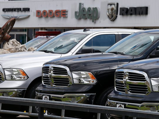 Ram pickup trucks sit on a dealership lot in Fairfield,