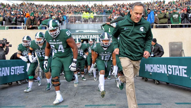 Michigan State football coach Mark Dantonio leads the Spartans out of the tunnel before their game against Penn State in 2017.