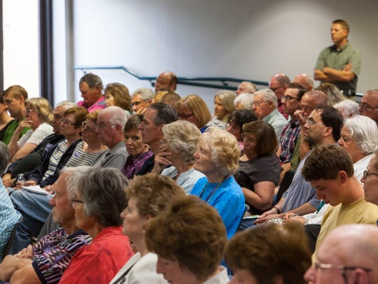 Community members listen to a debate for city council