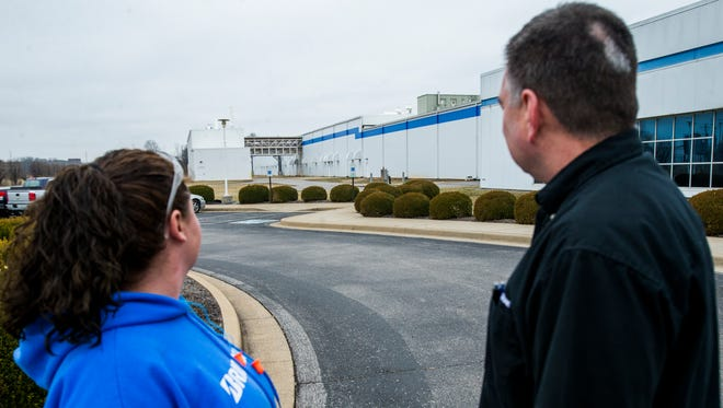 From left, Michele Rye, a Team Leader in production and Vance Merritt, Plant Manager of Bridgestone Metalpha, look back to the large plant located in Clarksville.