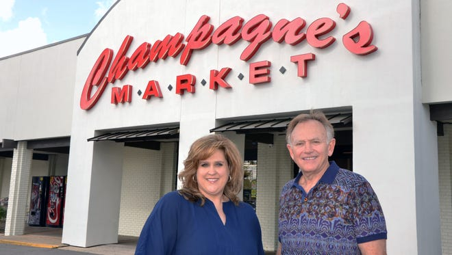 Owner Greg Champage and advertising and marketing director Jennifer Koenig  pose in front of  Champagne's Market after receiving the Associated Grocers award for 30 years as an Associated Grocer.