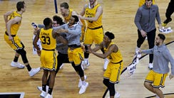 The UMBC Retrievers celebrate beating the Virginia
