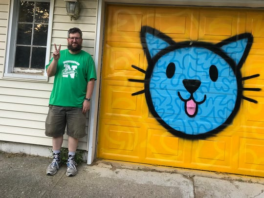 Carl Oxley III poses next to a cat he painted onto