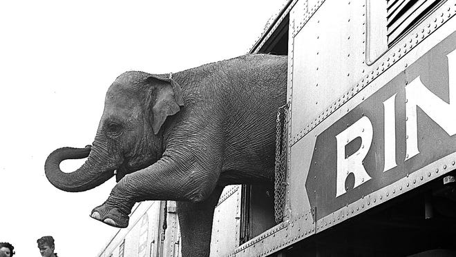 In this April 1, 1963 file photo, a Ringling Bros. Circus elephant walks out of a train car as young children watch in the Bronx railroad yard in New York. The Ringling Bros. and Barnum & Bailey Circus closed in May 2017, after 146 years of performances and travel. New York is looking to ban the use of elephants in any performance.