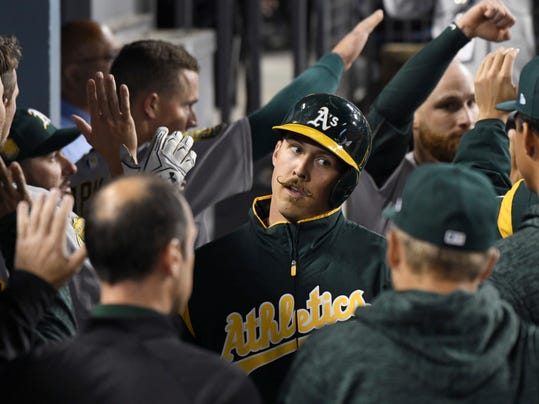 Oakland Athletics pitcher Daniel Mengden, center, is congratulated in the dugout after scoring on a hit by Marcus Semien during the fourth inning of a baseball game against the Los Angeles Dodgers, Wednesday, April 11, 2018, in Los Angeles. (AP Photo/Michael Owen Baker)