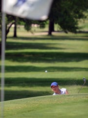 Randi Romack of Austin blasts out of a sand trap and