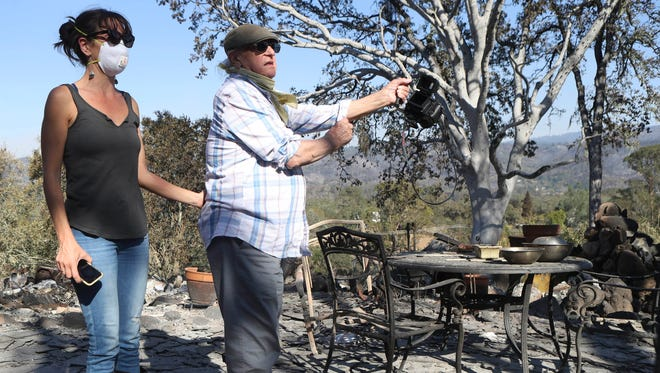 Sarah Ashton, left, and her dad Stephen Ashton, take a look at their family home and vineyard for the first time after the Nuns fire destroyed the property in Glen Ellen, Calif.