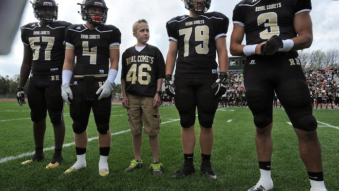 Landon Brice (46) served as Rush-Henrietta's honorary captain for the coin flip prior to Saturday's matchup with Monroe County rival Pittsford. R-H lost, 36-33.
