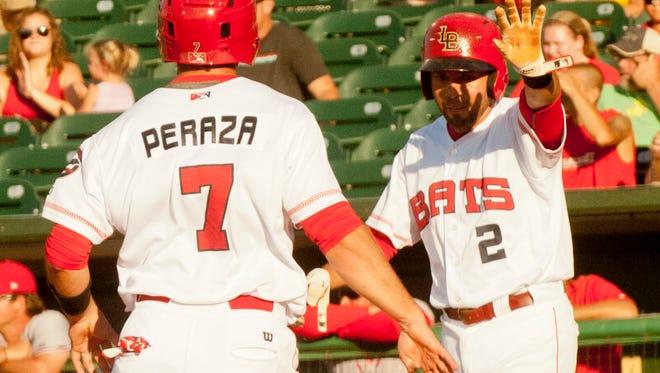 Louisville Bats' Hernan Iribarren waits at home plate to give Bats' Jose Peraza a high five as both score on a hit by Louisville Bats' Scott Schebler in the bottom of the 1st inning.13 June, 2016
