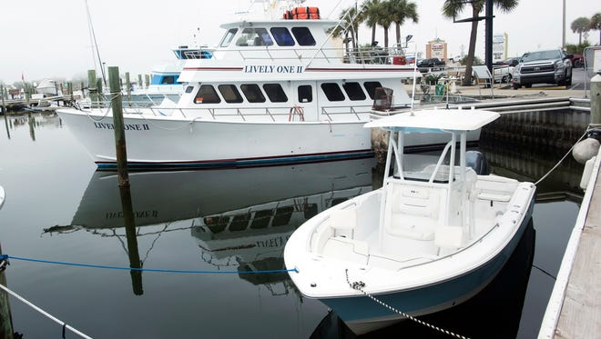 Commercial sports fishing vessels sit idle Tuesday, Dec. 19, 2017, at the docks at the Pensacola Beach Marina.
