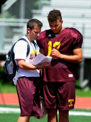 Mike Rowe converses with defensive end Chance Bowen at an afternoon practice on Monday, June 20, at St. Johns University.