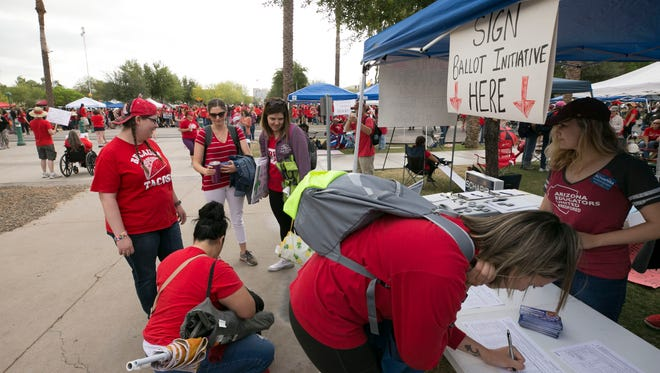 Allie Lewis (right), a third-grade teacher at Chandler Unified School District, signs a petition for the Invest in Education ballot initiative during the fifth day of the Arizona teacher walkout at the state Capitol in Phoenix on May 2, 2018.