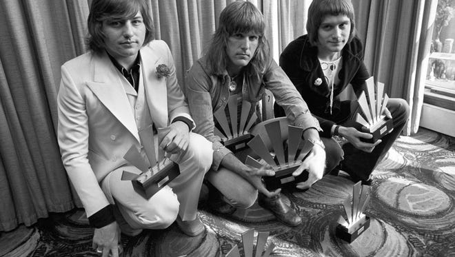 "FILE - This is a Sept. 30, 1972  file photo of  the members of the rock band Emerson, Lake and Palmer,Greg Lake, left Keith Emerson, centre, and Carl Palmer after an award ceremony in London . Greg Lake, the prog-rock pioneer who co-founded King Crimson and Emerson, Lake and Palmer, has died. He was 69. Lake died Wednesday Dec, 7, 2016 after ""a long and stubborn battle with cancer,"" according to his manager. (PA File via AP)"