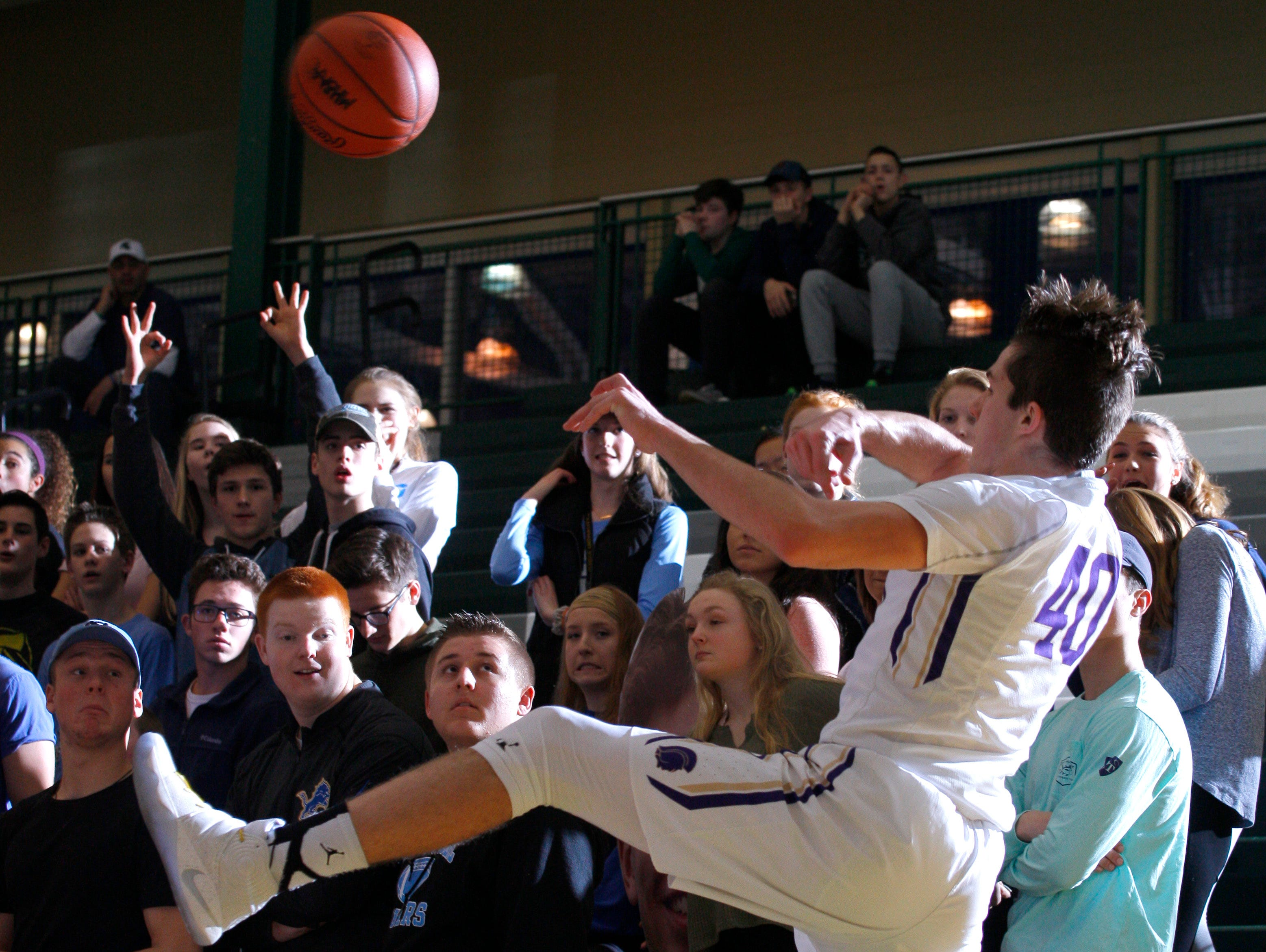 Fowlerville's Geoffrey Knaggs leaps to tap a deflected ball back to a teammate against Lansing Catholic during their district game Monday, March 6, 2017, in East Lansing, Mich. Fowlerville won 66-52.