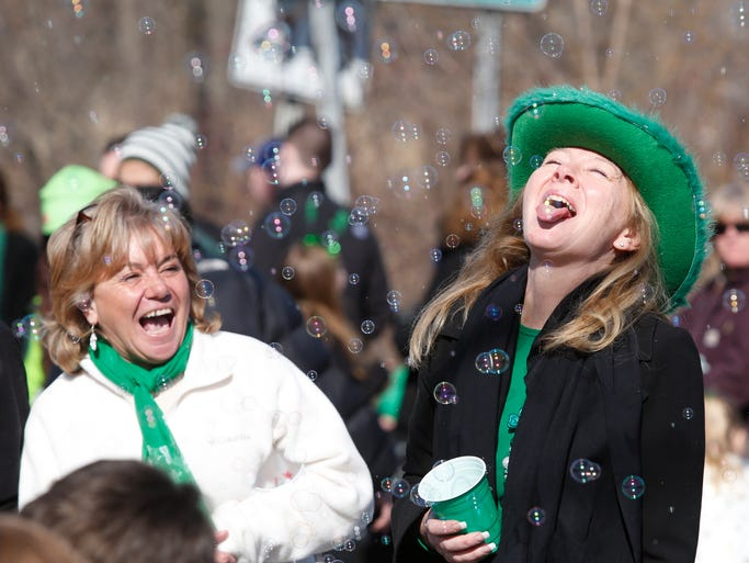 Maria Kelly watches her friend Elizabeth McDermott catch a bubble at the 38th Annual Northern Westchester - Putnam County St. Patrick's day parade in Mahopac on March 9, 2014.