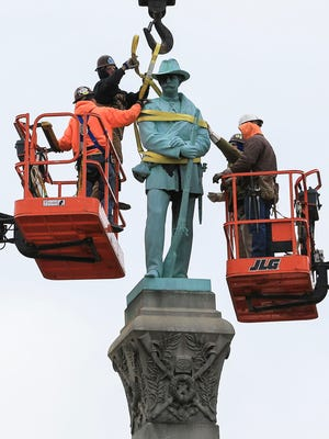 Messer Construction crews prepare the large Confederate monument for dismantling from the base Saturday morning on Third Street. The Confederate monument -- to honor confederate soldiers killed in the Civil War -- was first installed on Third Street in 1895. The monument is being moved to Brandenburg.