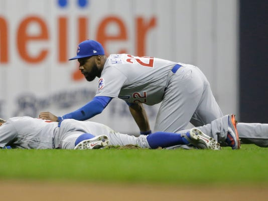 Chicago Cubs' Jason Heyward (22) checks on Javier Baez after they collided trying to catch a hit off the bat of Milwaukee Brewers' Hernan Perez during the sixth inning of a baseball game Friday, April 7, 2017, in Milwaukee. Baez left the game after the collision. (AP Photo/Jeffrey Phelps)