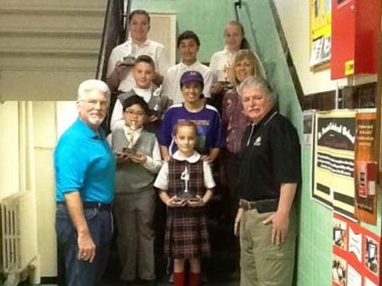 Pictured are St. Francis Cathedral School students who were winners of the Metuchen Elks #1914 District Basketball Hoops Contest.. Top of the stairs left to right are:  Olivia Patikowski, Abbas Choman and Mackenzie Bloss.  Middle row:  Robert Roma, Carolyn Roberts, Physical Education Teacher and Barbara Stevens, Principal.  In the front row are:  Gary Dengelegi, Metuchen Elks, Francis Regis, Paige Logan and Mike Walsh of the Elks.