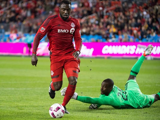 Toronto FC forward Jozy Altidore (17) drives the ball around D.C. United goalkeeper Bill Hamid (28) to score during the first half of an MLS soccer match Saturday, Oct. 1, 2016, in Toronto. (Nathan Denette/The Canadian Press via AP)