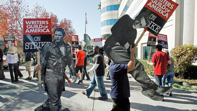 Striking writers in November 2007, carrying life-sized photos of legendary actors, Marlon Brando, left, and James Dean outside Raleigh Studios in Los Angeles.