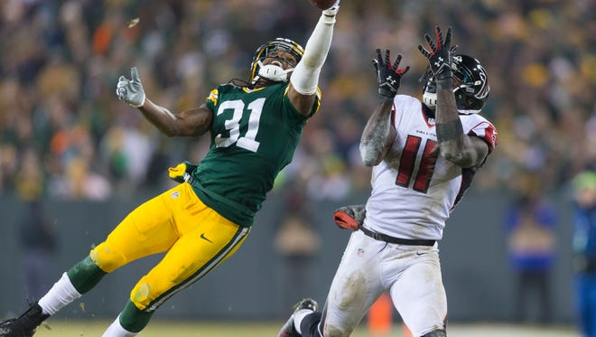 Green Bay Packers cornerback Davon House (31) breaks up the pass intended for Atlanta Falcons wide receiver Julio Jones (11) during a December 2014 game at Lambeau Field.