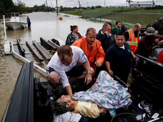A rescuer moves Paulina Tamirano, 92, from a boat to a truck bed as people evacuate from rising waters from Tropical Storm Harvey Aug. 29, 2017 in Houston.