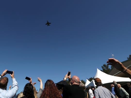 Mourners look to the sky for a military fly-over at the funeral of local U.S. Air Force Staff Sgt. Carl Enis, who was among seven crew members killed in a helicopter crash in Iraq, during a celebration of his life at the Ayavalla Plantation on Saturday, March 31, 2018.