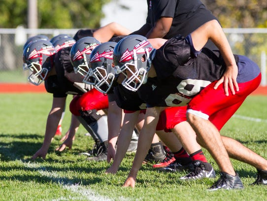 The Port Huron Big Reds run drills at a football practice